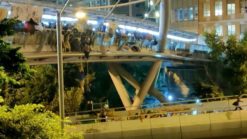 Dozens of Hong Kong protesters escape a two-day police siege at a university campus by shimmying down a rope from a bridge to awaiting motorbikes