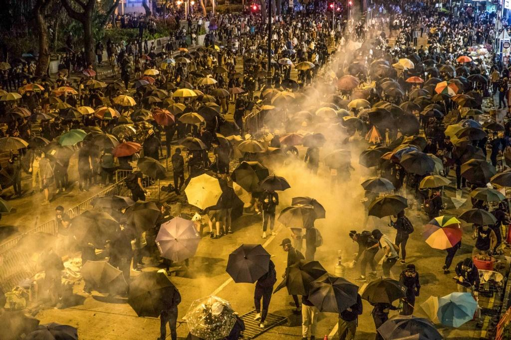 Protesters react as police fire tear gas while they attempt to march towards Hong Kong Polytechnic University