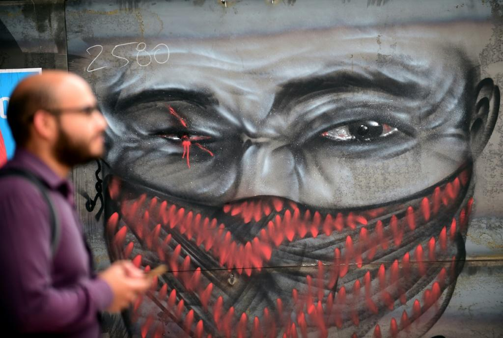A man walks by graffiti depicting a demonstrator with an injured eye, in clear reference to those hurt in recent clashes, on November 18