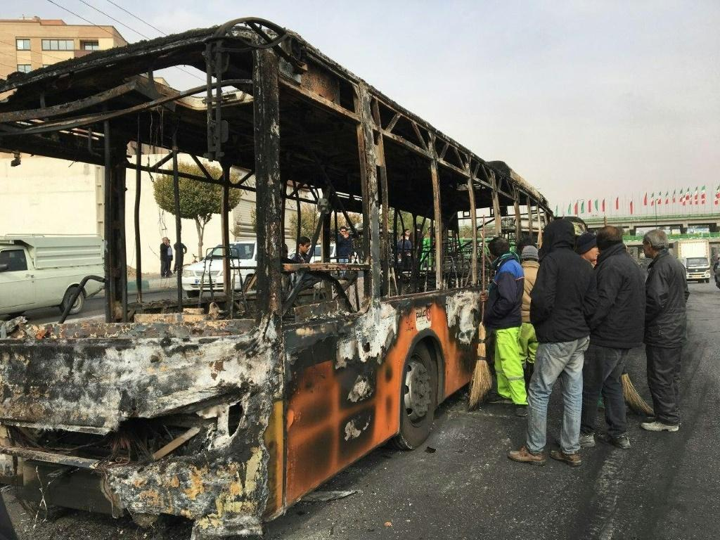 Iranians inspect the wreckage of a bus that was set ablaze by protesters in the central city of Isfahan
