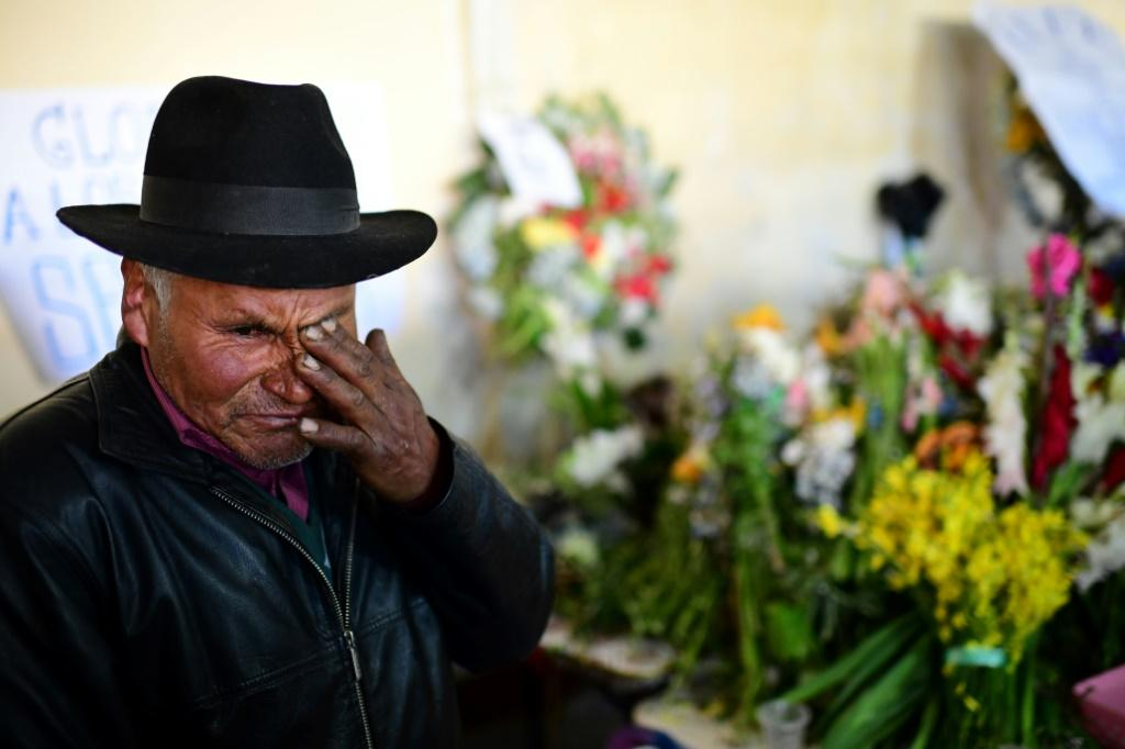 A man mourns during the funeral of eight supporters of Bolivia's ex-President Evo Morales, killed when security forces lifted a siege on a fuel plant, in El Alto on November 21, 2019 Bolivia's interim President Jeanine Anez asked Congress Wednesday to ap