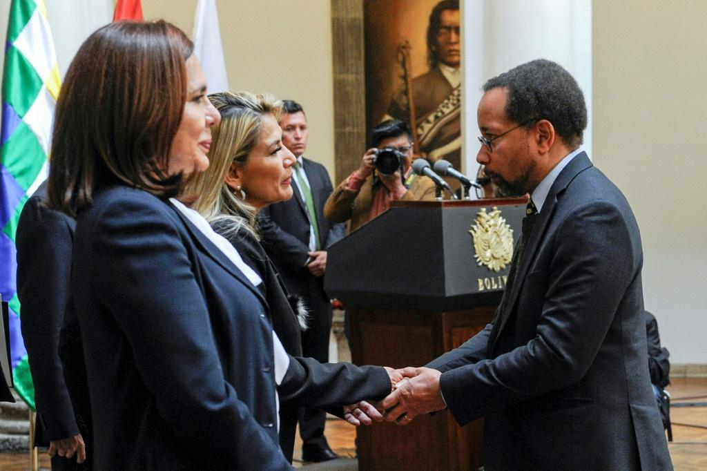 Anez (2-L) is greeted by the US Charge d'Affaires in Bolivia, Bruce Williamson at Quemado presidential palace in La Paz on November 22, 2019