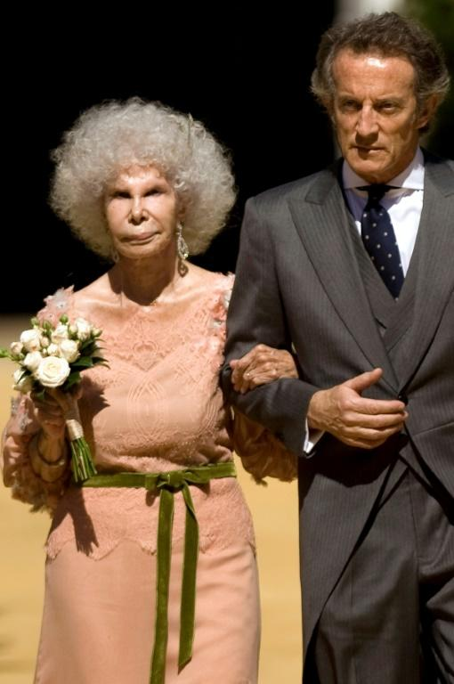 Spain's Duchess of Alba, Maria del Rosario Cayetana Fitz-James-Stuart and her husband Alfonso Diez walk towards photographers after their wedding ceremony at the Palacio de las Duenas in Sevilla on October 5, 2011.
