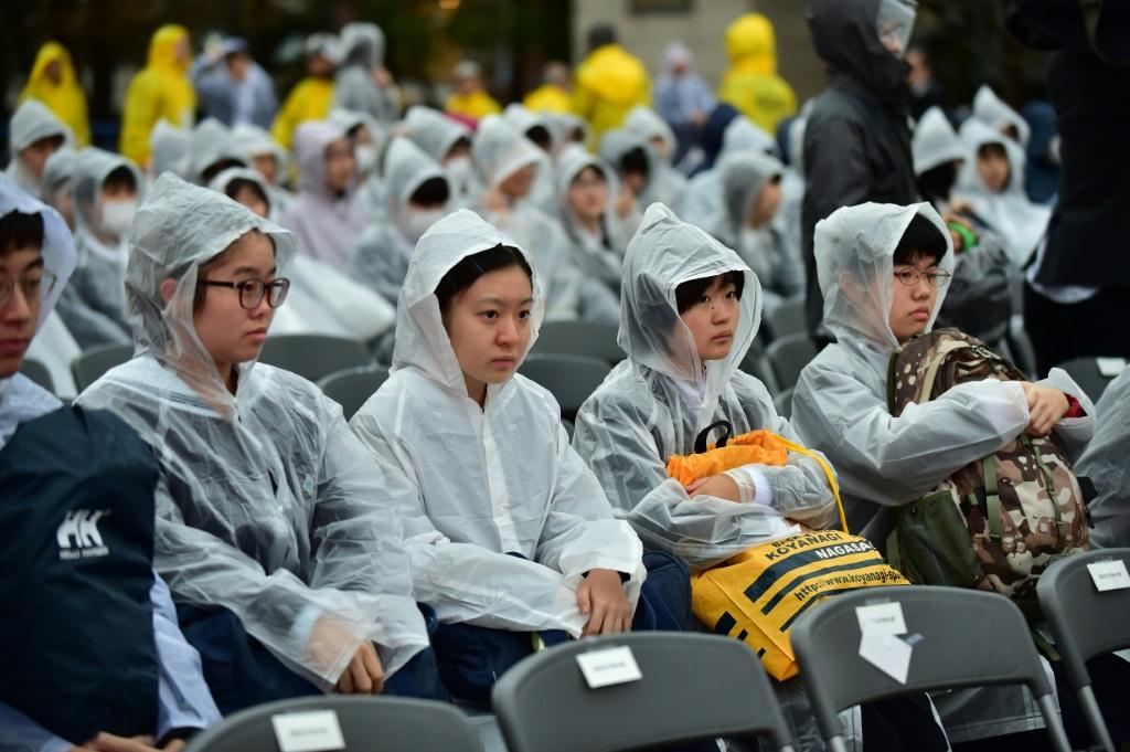 Hundreds of people in white waterproofs stood in torrential rain to hear the pope's speech