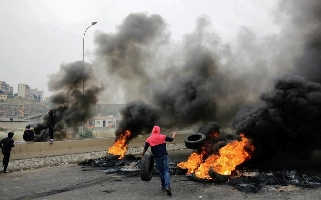 Lebanese anti-government protesters burn tyres as they block a road in the northern city of Tripoli on November 25, 2019