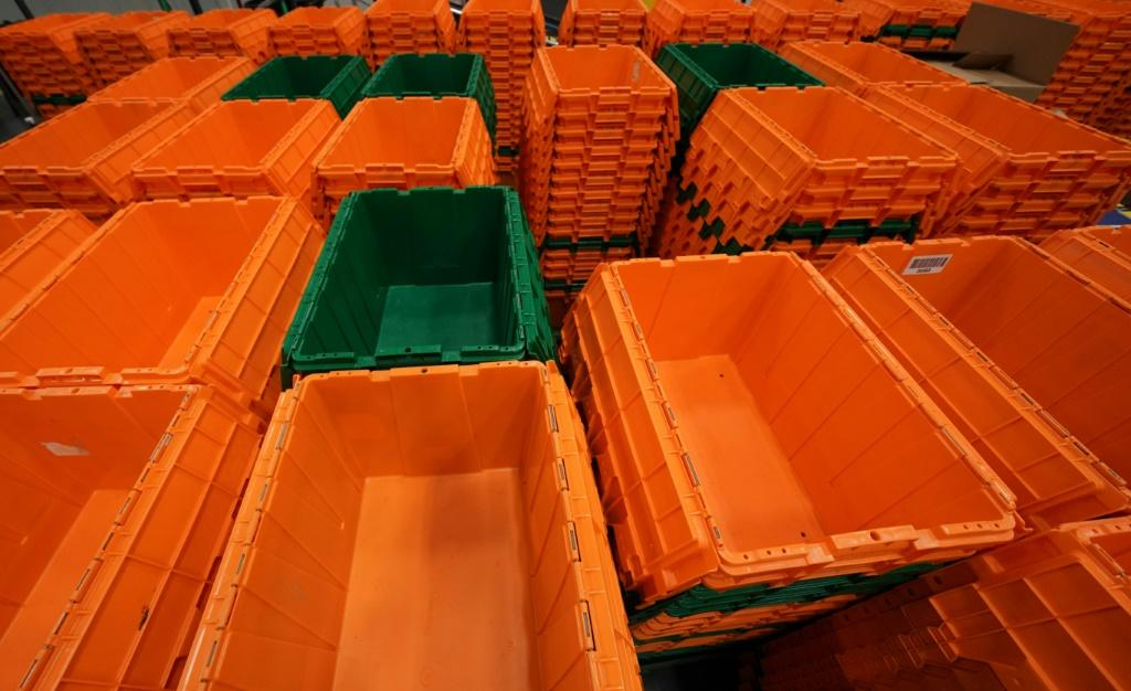 Orange and green plastic bins -- the company's signature colors -- zip along on conveyor belts overhead