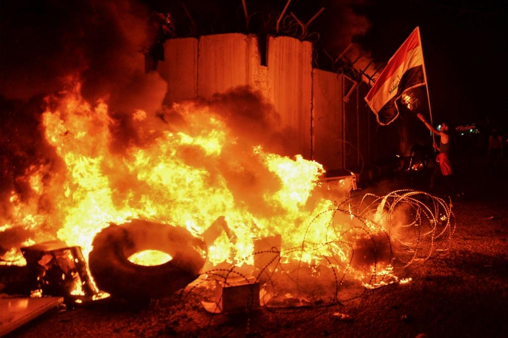 The Iraqi flag is brandished by demonstrators after they set fire to Iran's consulate in Najaf