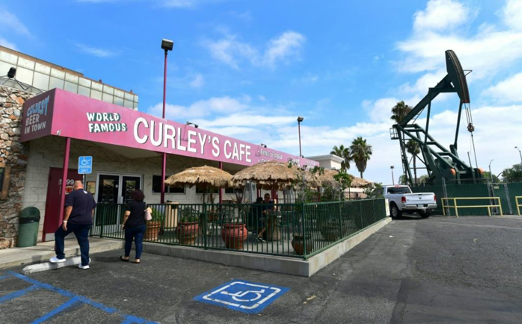 People make their way into Curley's Cafe in Signal Hill, which sits in the shadow of a pumpjack