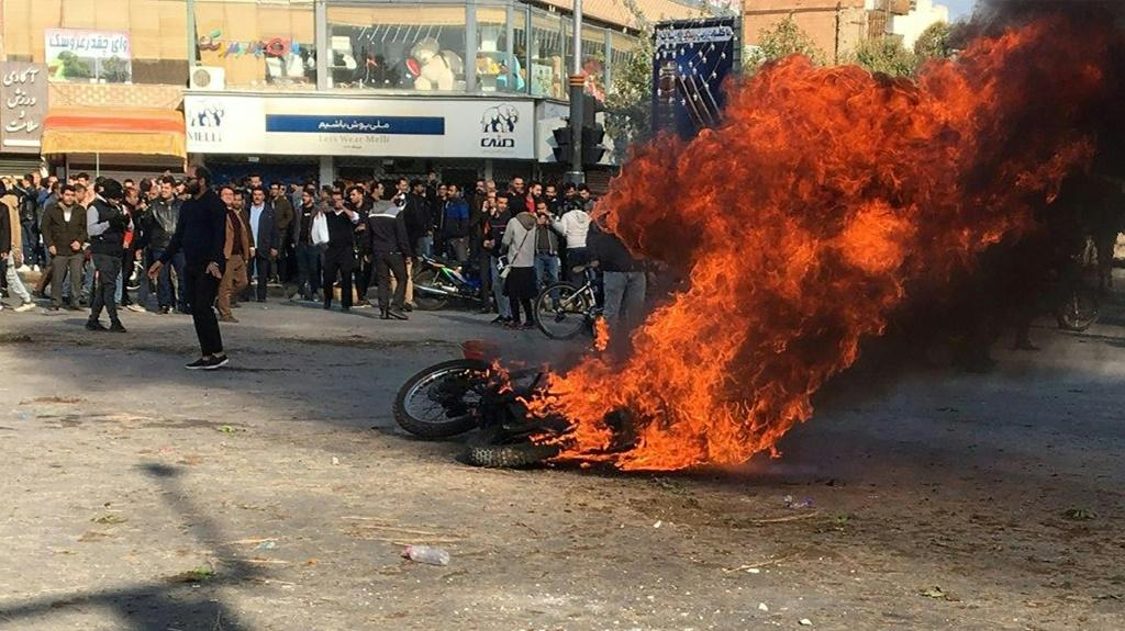 Iranian protesters gather around a burning motorcycle in the city of Isfahan during a demonstration last month against an increase in fuel prices