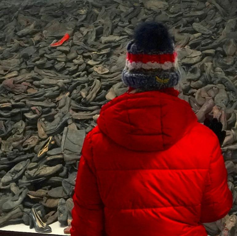 A visitor to Auschwitz stands in front of victims' shoes