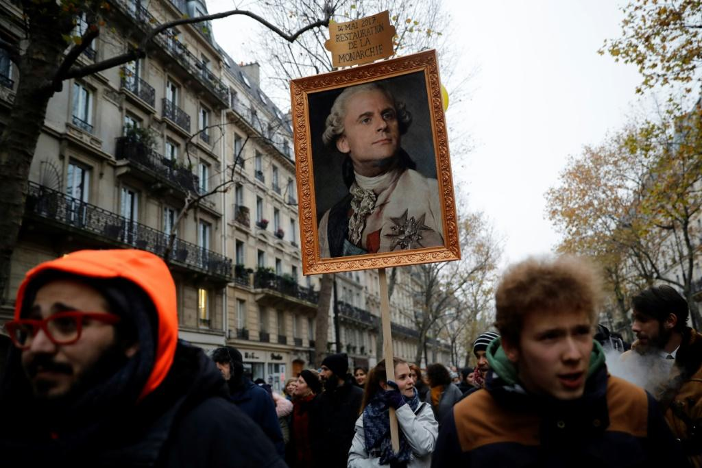 "A Paris protester carries a portrait of Emmanuel Macron depicted as royalty that says ""May 14, 2017, restoration of the monarchy"" -- a reference to his election date"