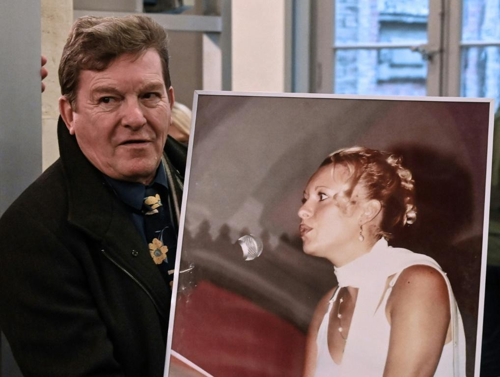 Jacky Kulik holds a portrait of his daughter Elodie who was kidnapped, raped, strangled and her corpse then burned in northern France in January 2002