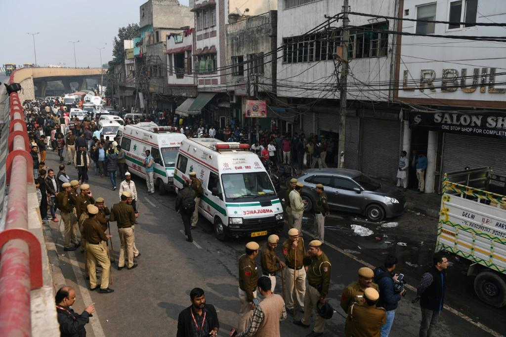 Police personnel and ambulances line up to aid victims of the deadly blaze that ripped through a four-storey bag factory in New Delhi