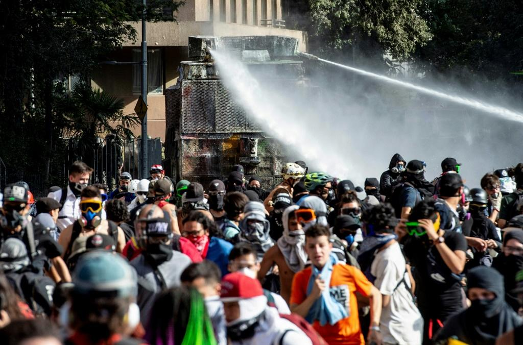 Demonstrators are sprayed by riot police with water cannons during clashes in a protest against President Sebastian Pinera's government in Santiago, on December 10