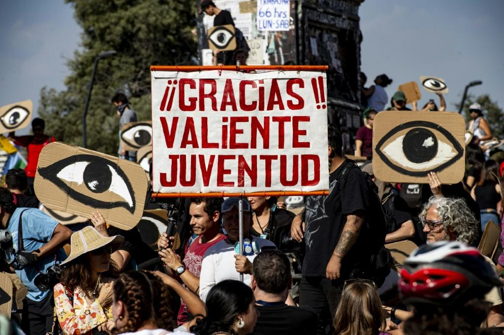 """Demonstrators hold placards depicting eyes -- in reference to protesters' eyes damaged by pellets -- and a sign reading """"Thanks, brave youth"""" during a protest in Santiago, on December 10"""