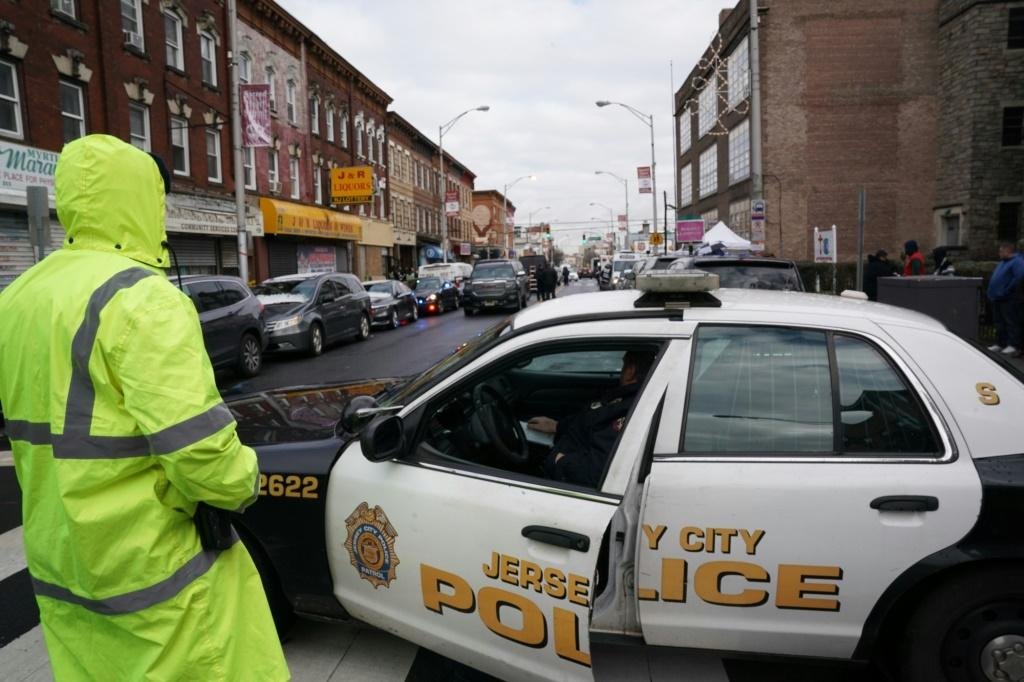 Police gather evidence a day after a deadly shooting at a Jewish deli in the New York suburb of Jersey City
