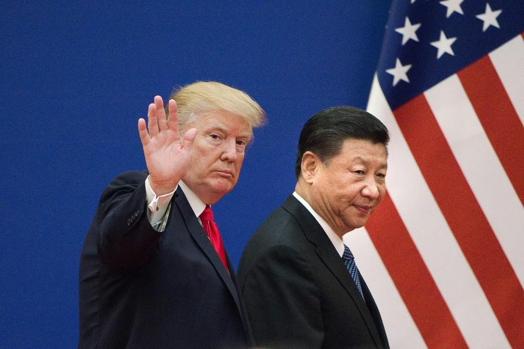 This file photo taken on November 09, 2017 shows US President Donald Trump and China's President Xi Jinping leaving a business leaders event at the Great Hall of the People in Beijing