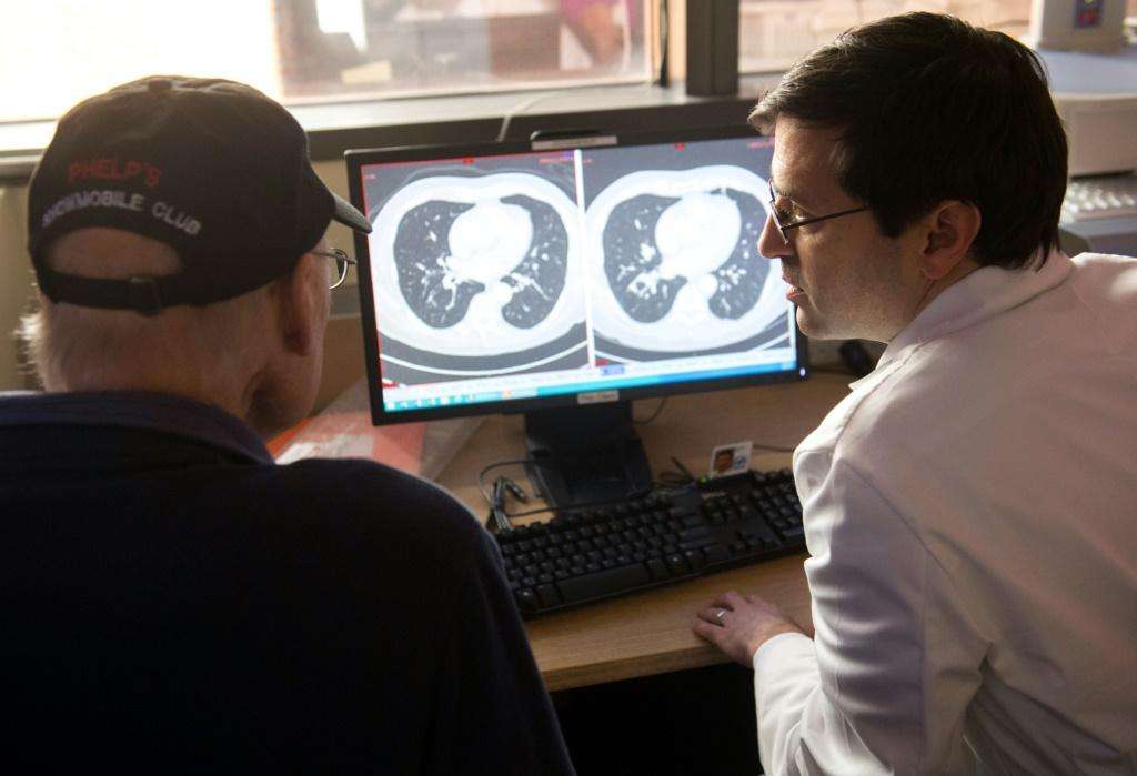 Dr. Christian Hinrichs (R), an investigator at the National Cancer Institute in immunotherapy for HPV+ cancers, shows a survivor of metastatic cancer the difference between his CT scan showing cancerous tumors and a clean scan after treatment