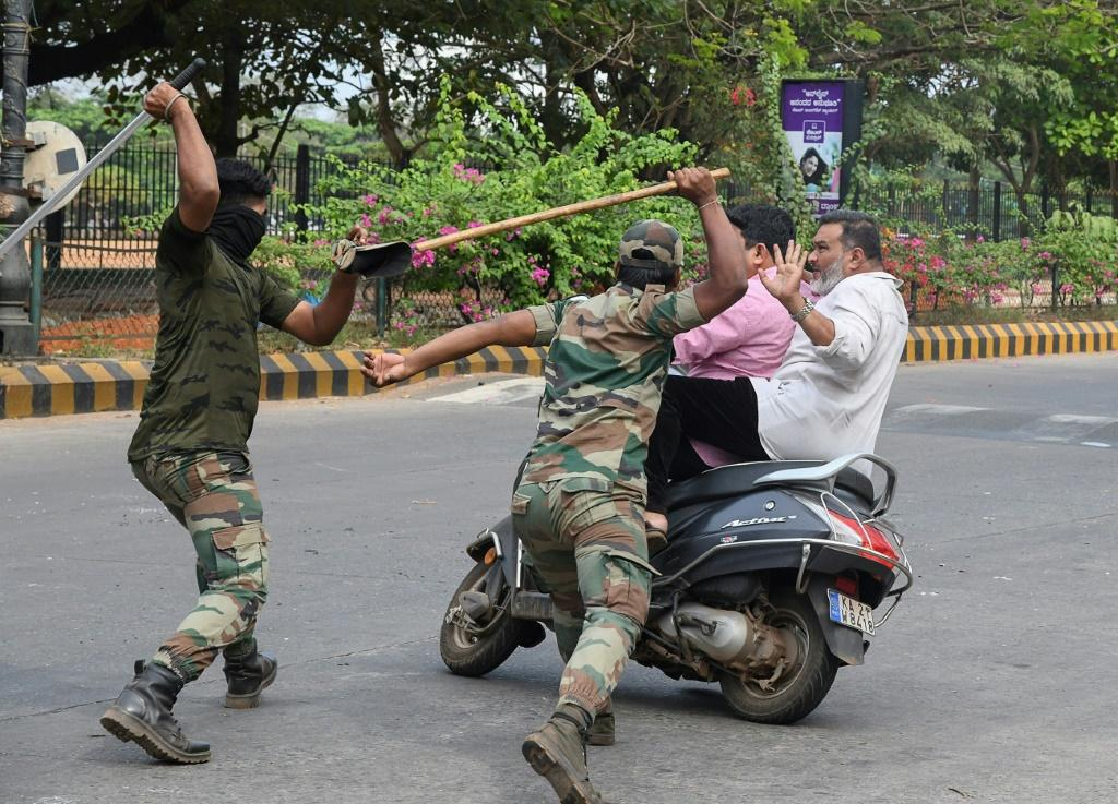 Karnataka Reserve Police Force members prepare to club two men who rode too close to a street barricade in Mangalore