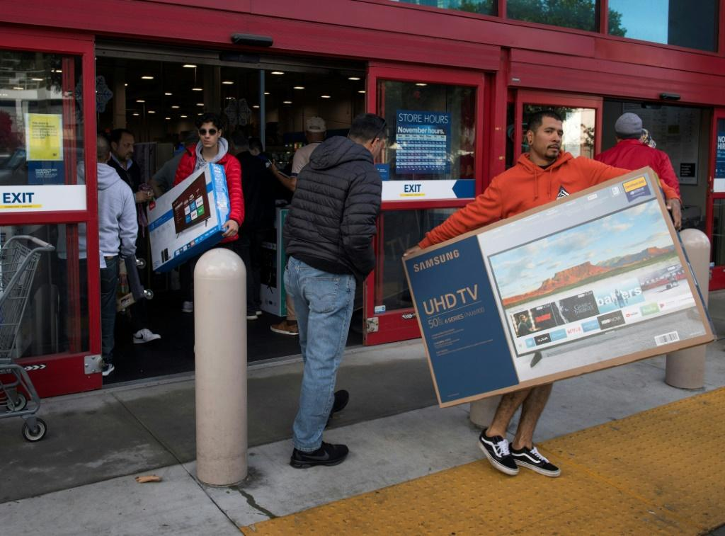 Shoppers carry televisions purchased from a store during Black Friday sales in Los Angeles