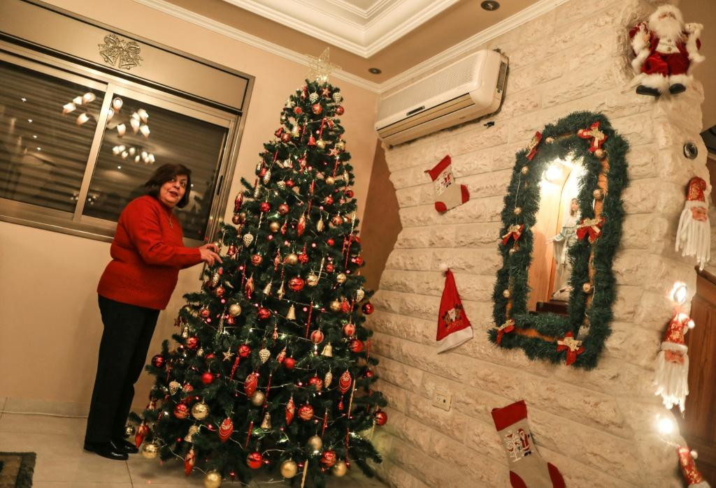 Christian Gaza resident Hanadi Missak adjusts the ornaments on her Christmas tree at her home in Gaza City, but she could not travel to Bethlehem this year as Israeli authorities did not grant a permit in time