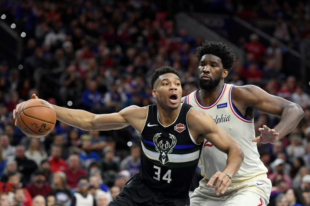 Milwaukee's Giannis Antetokounmpo (L) looks to pass as Philadelphia's Joel Embiid defends in the 76ers' 212-109 NBA victory over the Bucks
