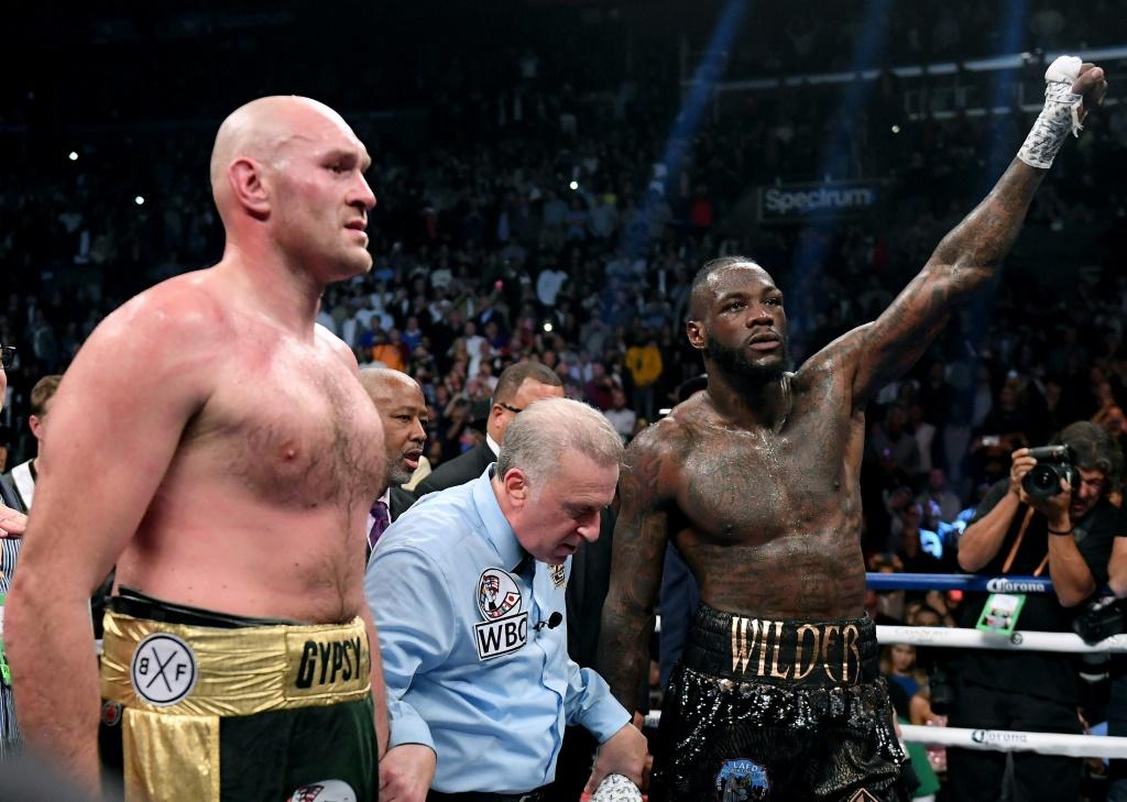 Tyson Fury and Deontay Wilder wait for a decision with referee Jack Reiss before a draw is announced in their WBC heavyweight world title fight in Los Angeles on December 1, 2018