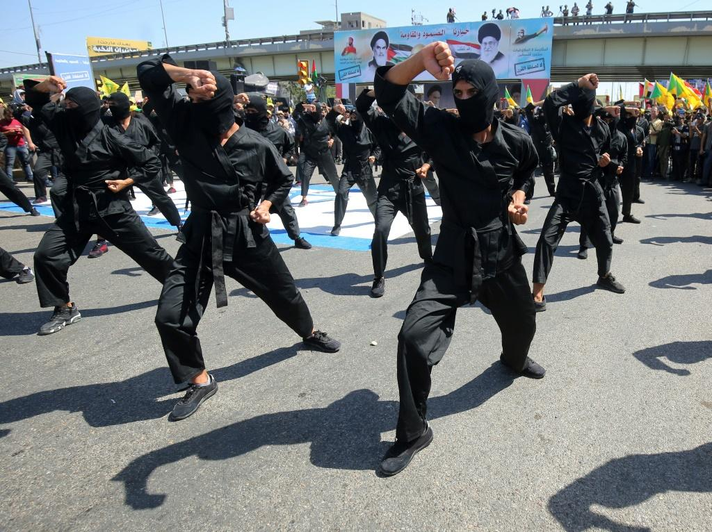 A picture taken on May 31, 2019 shows Iraqi Shiite fighters from the Iran-backed armed group, Hezbollah brigades take part in a military parade to mark the pro-Palestinian Al-Quds (Jerusalem) Day in Baghdad
