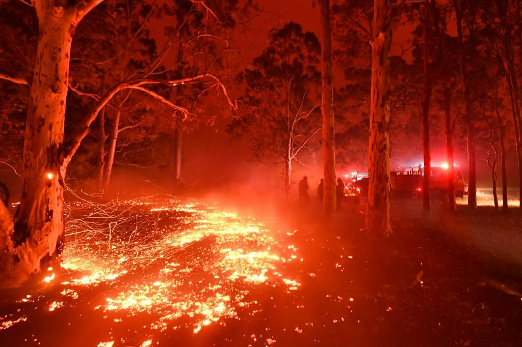Burning embers cover the ground as firefighters battle against bushfires around the town of Nowra in the Australian state of New South Wales on December 31, 2019