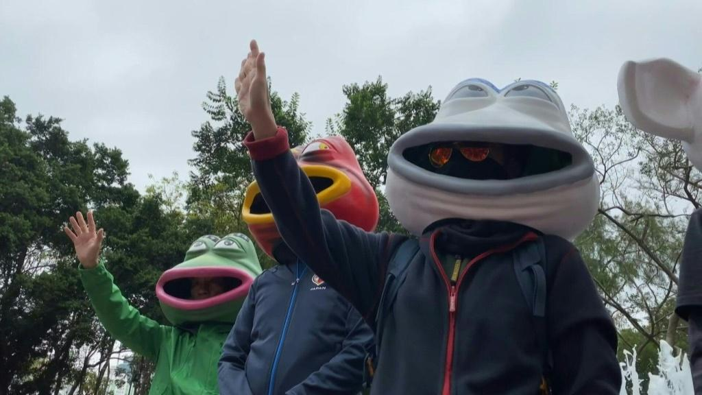 IMAGESPeople sporting various Pepe the Frog masks get ready to take part in a huge pro-democracy march in Hong Kong. The city has been battered by more than six months of unrest with millions marching, as well as confrontations in which police have fired