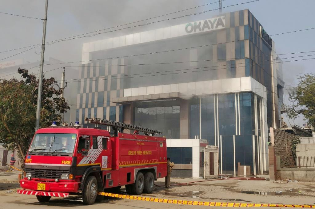 A Delhi fire truck is parked next to the site of a fire and building collapse