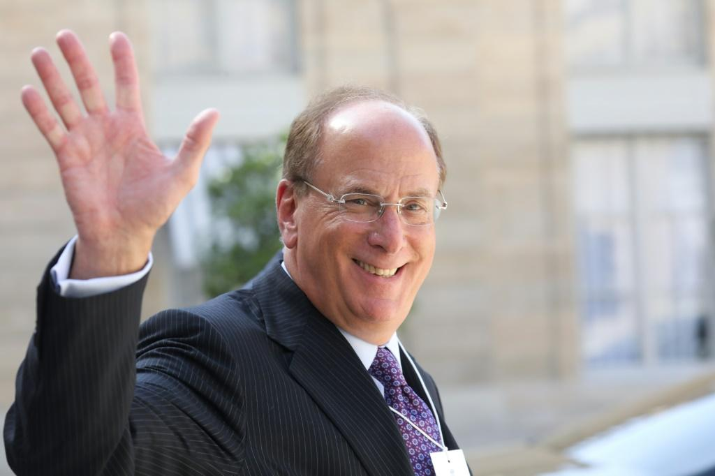 CEO Larry Fink waves as he leaves a meeting about climate action investmentsat the Elysee Palace in Paris in July 2019