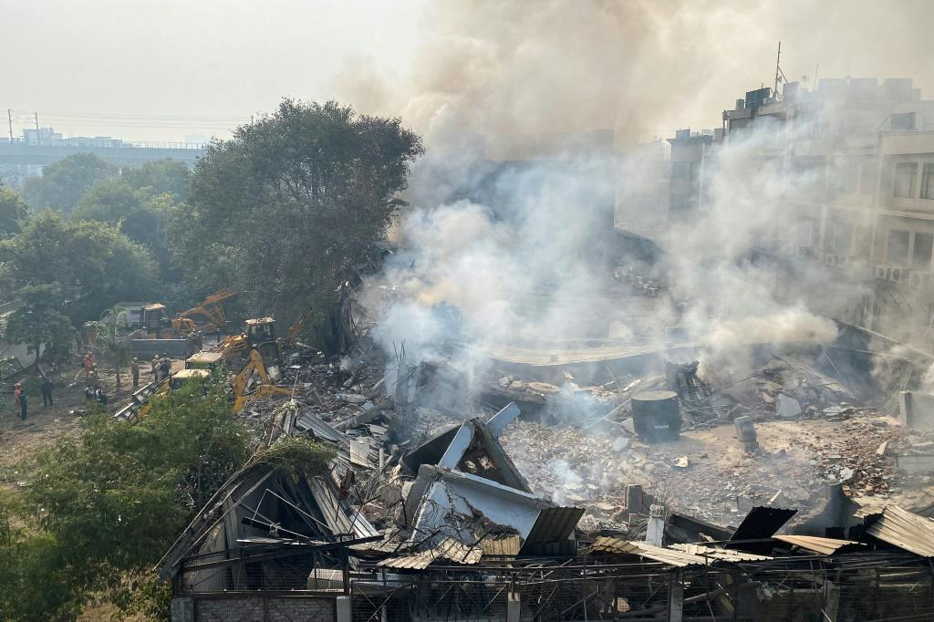 Smoke rises over the debris of a building that collapsed during a fire in New Delhi