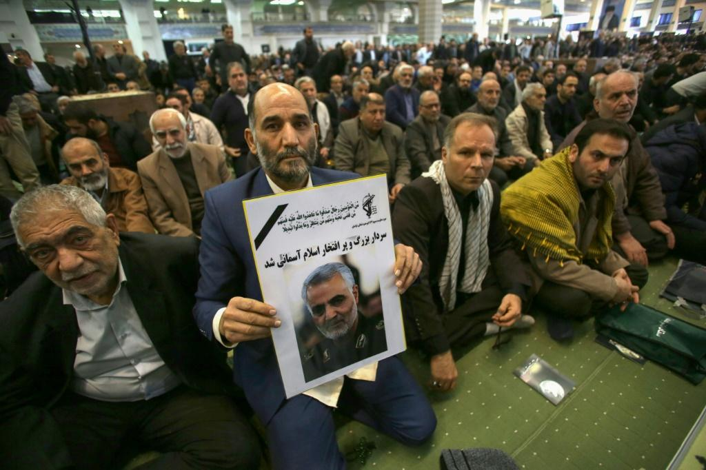 "An Iranian man holds a poster of slain Iranian Revolutionary Guards Qasem Soleimani during a special prayer ceremony in Tehran to mourn the ""martyr"" killed in a US strike in Baghdad"