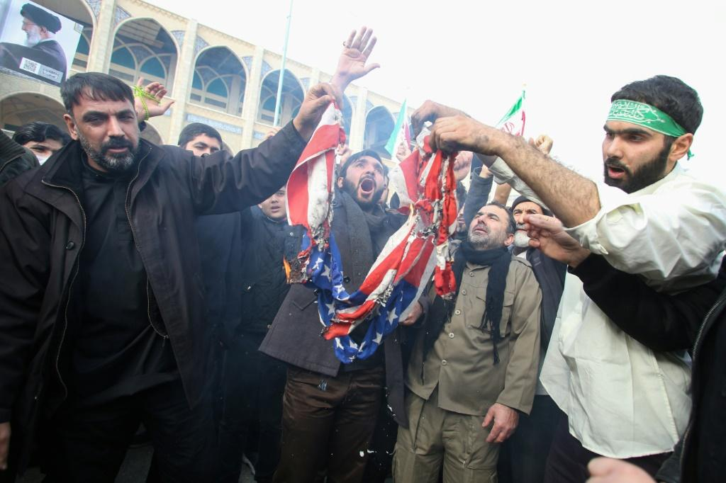 "Iranians burn a US flag during a demonstration against American ""crimes"" in Tehran on January 3, 2020 following the US attack that killed Soleimani"