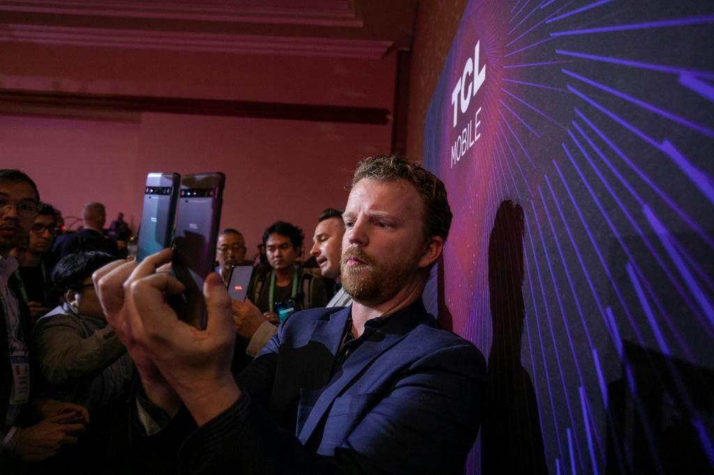 A man uses a new TCL 10 series phone at the TCL news event during the 2020 Consumer Electronics Show (CES) in Las Vegas