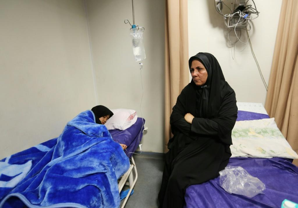 An Iranian woman sits next to a relative injured in the stampede