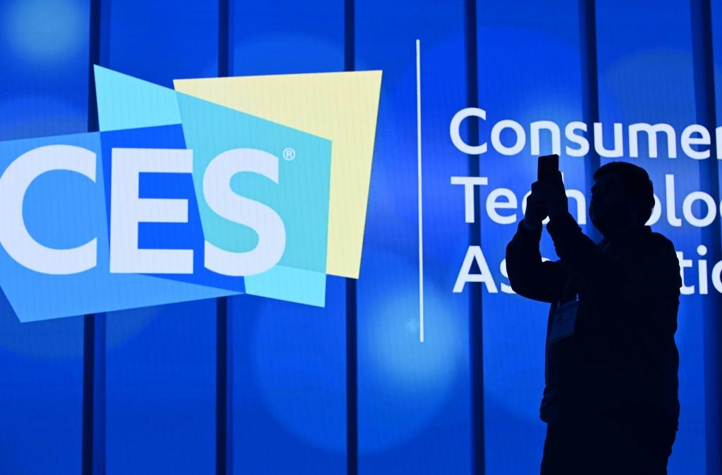 An attendee photographs a sign next to the CES logo ahead of the first keynote address at the 2020 Consumer Electronics Show in Las Vegas, Nevada