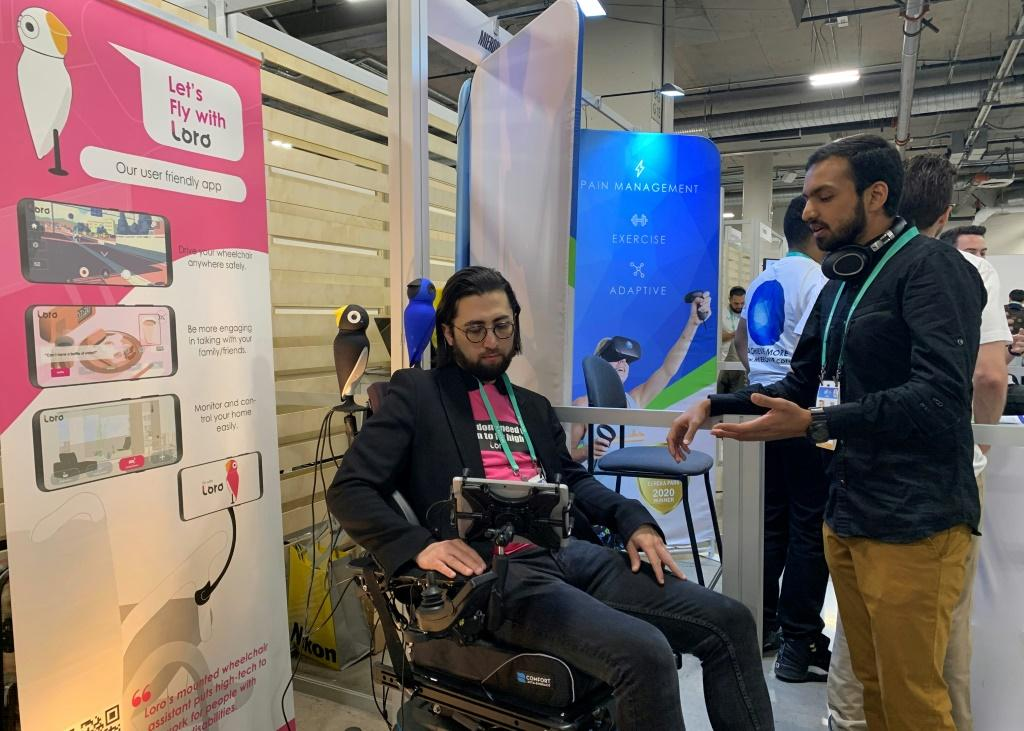 David Hojah (L), cofounder and CEO of Loro, shows the robot assistant for the wheelchair-bound at the 2020 Consumer Electronics Show