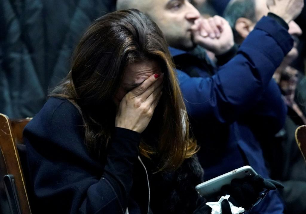 A woman weeps during a memorial service at the University of Toronto in Toronto, Ontario on January 12 for the victims of Ukrainian Airlines flight 752 which was shot down over Iran