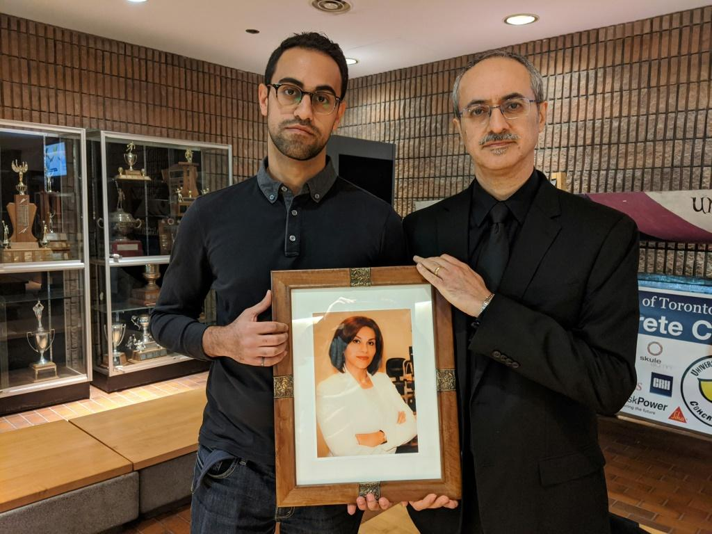 Amirali Alavi (L) holds a picture of his mother Neda Sadighi, one of the victims of Ukrainian Airlines flight 752, with his father Farzad Alavi (R) at his side on January 12, 2020 at the University of Toronto, Canada