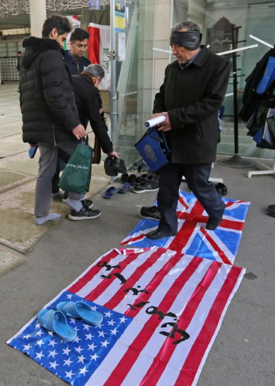 A supporter of the Basij, a militia loyal to the Islamic republic's establishment, walks over a Union Jack and US flag as he arrives at a memorial for victims of the Ukraine plane crash