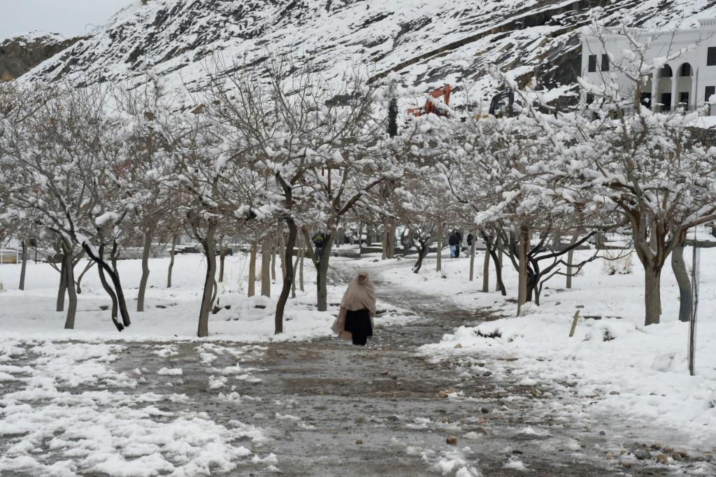 A woman walks down a path in Quetta, Pakistan, after heavy snow