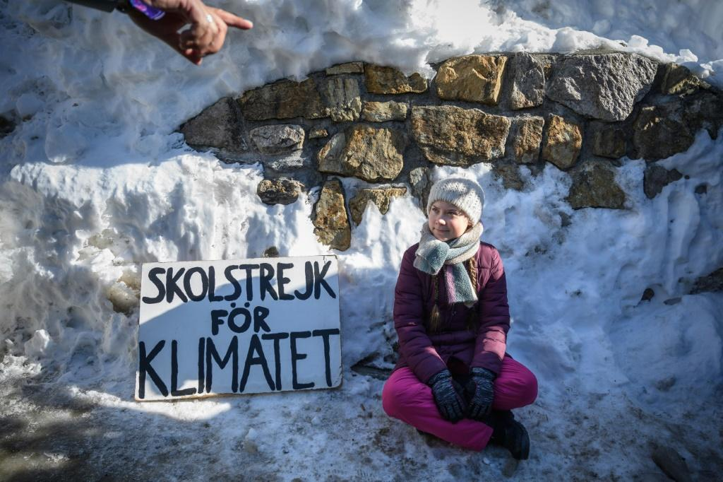 """Swedish youth climate activist Greta Thunberg, seen here at the 2019 World Economic Forum sitting next to a placard reading """"school strike for climate"""", will also be at the event this year"""