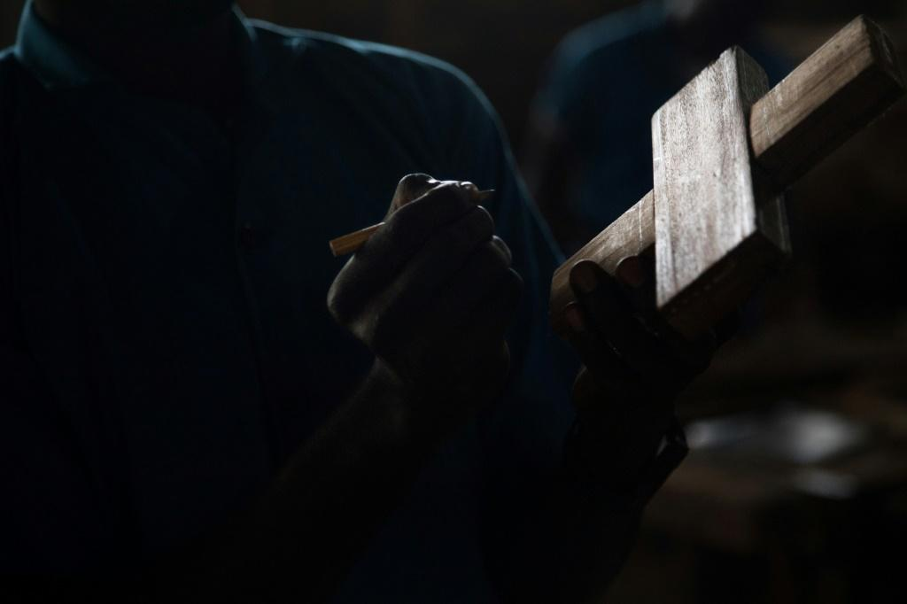 A former child soldier on a carpentry course draws a cutout on a piece of wood