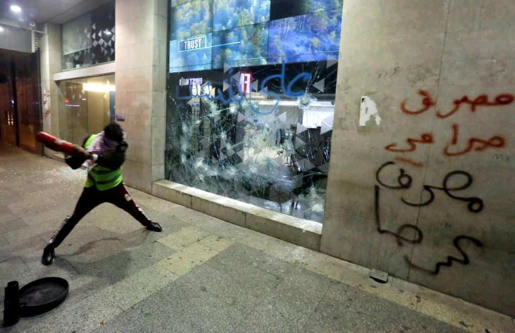 "A Lebanese protester smashes the window of a bank in Beirut, with graffiti on the wall reading ""banks are thieves"", as demonstrators demand an end to a months-long political vacuum, with police firing tear gas at the start of a ""week of wrath"