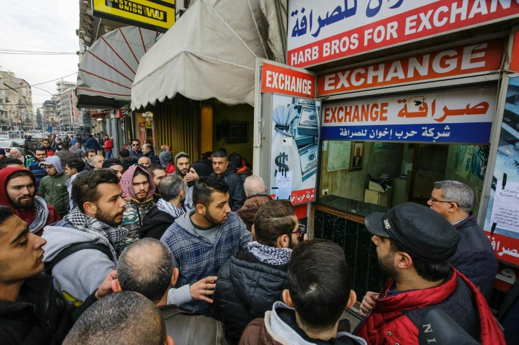 Lebanese anti-government protesters gather at the entrance of a currency exchange bureau in the northern port city of Tripoli