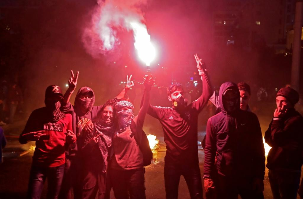 Lebanese anti-government protesters light a flare during ongoing demonstrations in Lebanon's capital Beirut on January 15