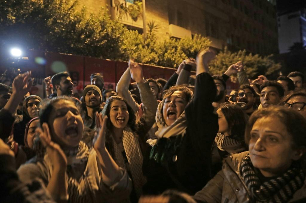 Lebanese demonstrators chant slogans against informal capital controls in front of the central bank in Beirut