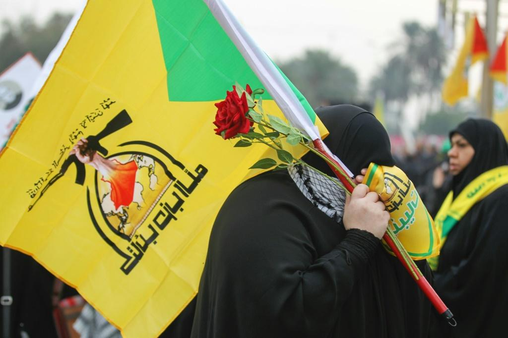 A supporter holding the flag of Hezbollah, which the UK government designated as a terror organisation